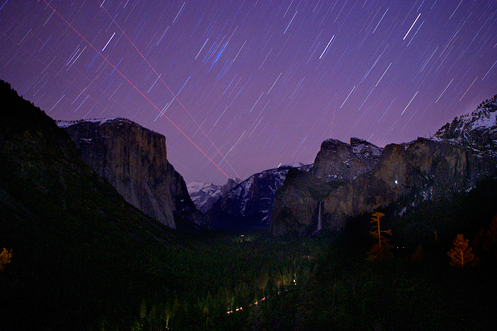 Yosemite Vally at night; star trails and jet trails.