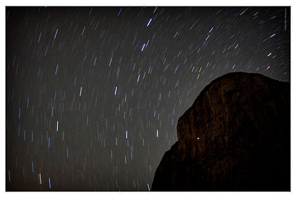 Night shot of El Capitan with star tracks.  the light dot on El Cap is the bivy lights from a climber. (photo by Tom Collins)